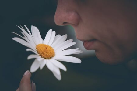 Young beautiful woman with flower, inhales the scent of chamomile
