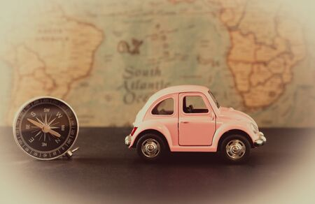 Little pink car and compass on vintage card background, travel concept Stockfoto