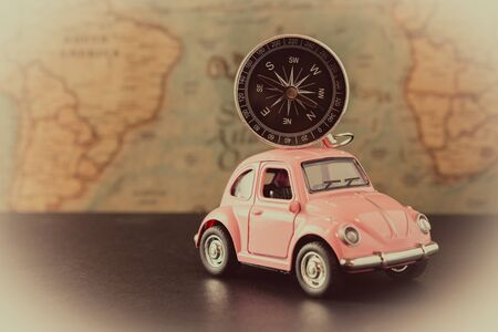 Small pink car with a compass on the roof on a background of vintage maps, travel concept Stockfoto