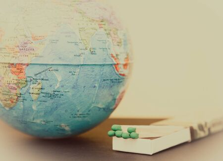 Matchstick and world globe on tinted background, concept of saving the planet from fire