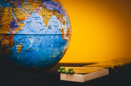World globe and matches on a tinted yellow background, the concept of saving the planet from fire, save the earth