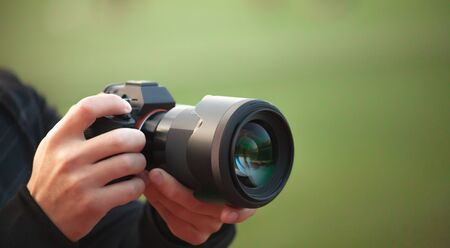 Photographer men shooting images. Man hands holding camera taking photos. Vivid blur green background