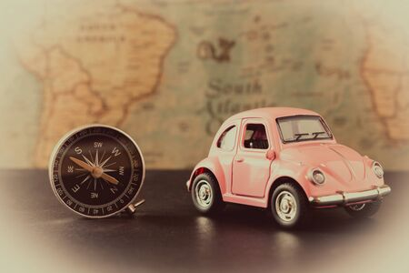 Little pink car and compass on vintage card background, travel concept, close-up