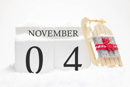Autumn calendar made of wooden cubes with the date of November 4, the concept of the first snow and future holidays. Close-up. Banque d'images