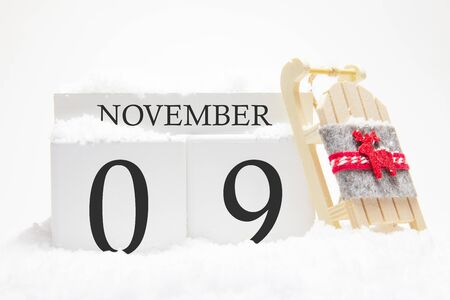 Autumn calendar made of wooden cubes with the date of November 9, the concept of the first snow and future holidays. Close-up. Imagens