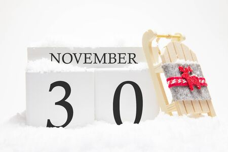 Autumn calendar made of wooden cubes with the date of November 30, the concept of the first snow and future holidays. Close-up.