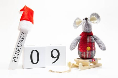 Wooden calendar with number February 9. Happy New Year! Symbol of New Year 2020 - white or metal (silver) rat. Christmas decorated.