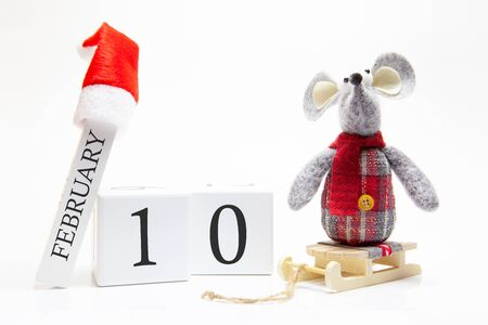 Wooden calendar with number February 10. Happy New Year! Symbol of New Year 2020 - white or metal (silver) rat. Christmas decorated. Stock Photo