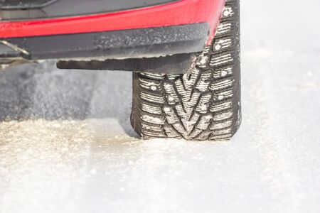 Detail of a tire on a winter road. Safe car driving concept.
