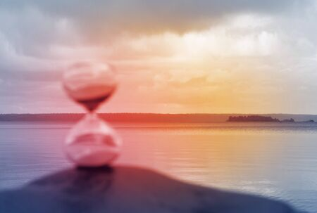 Blurred hourglass on a rock, illuminated in red as a concept of lost time.