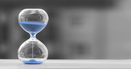 Hourglass with blue sand on a blurred black and white background, sand trending color