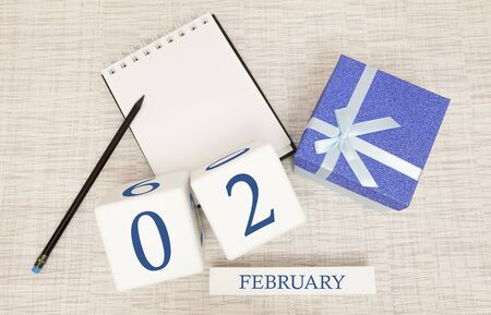 Calendar with trendy blue text and numbers for February 2 and a gift in a box.