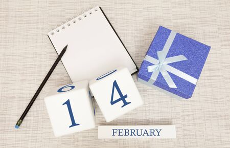 Calendar with trendy blue text and numbers for February 14 and a gift in a box.