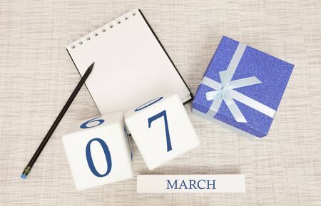 Calendar with trendy blue text and numbers for March 7 and a gift in a box.