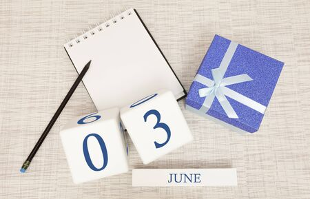 Calendar with trendy blue text and numbers for June 3 and a gift in a box.