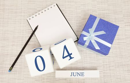 Calendar with trendy blue text and numbers for June 4 and a gift in a box.