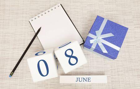 与时髦蓝色文本和数字的日历6月8日和在箱子的礼物。
