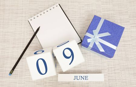 Calendar with trendy blue text and numbers for June 9 and a gift in a box.