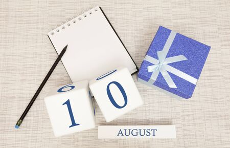 Calendar with trendy blue text and numbers for August 10 and a gift in a box.