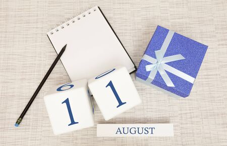 Calendar with trendy blue text and numbers for August 11 and a gift in a box.
