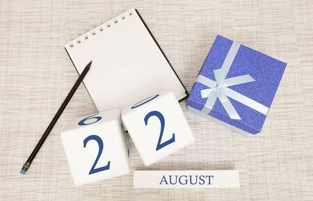 Calendar with trendy blue text and numbers for August 22 and a gift in a box.