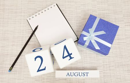 Calendar with trendy blue text and numbers for August 24 and a gift in a box.