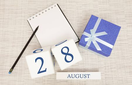 Calendar with trendy blue text and numbers for August 28 and a gift in a box.