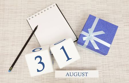 Calendar with trendy blue text and numbers for August 31 and a gift in a box.