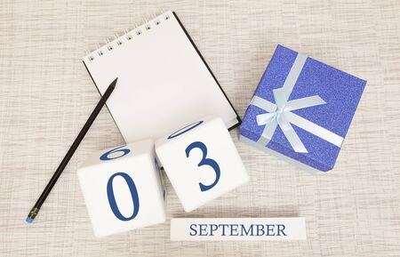 Gift box and wooden calendar with trendy blue numbers, September 3, business planner