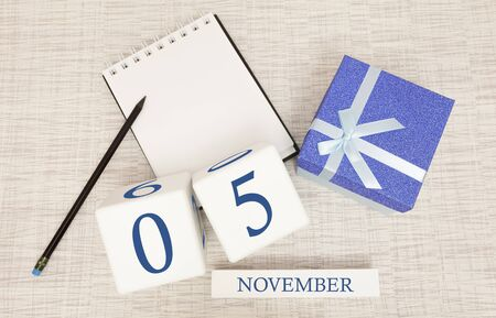 Notepad and wooden calendar for November 5, next to a blue gift box. Stock Photo