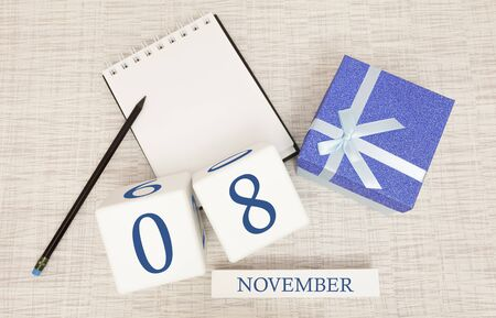 Notepad and wooden calendar for November 8, next to a blue gift box.