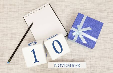 Notepad and wooden calendar for November 10, next to a blue gift box. Stock Photo