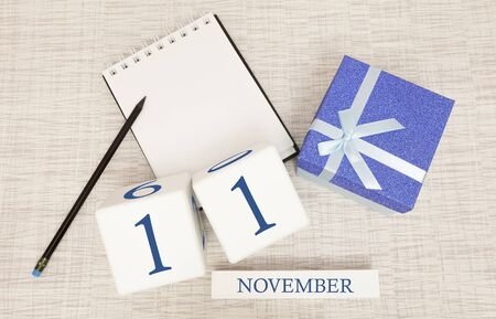 Notepad and wooden calendar for November 11, next to a blue gift box. Stock Photo