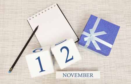 Notepad and wooden calendar for November 12, next to a blue gift box. Stock Photo