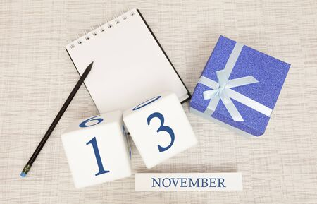 Notepad and wooden calendar for November 13, next to a blue gift box. Stock Photo