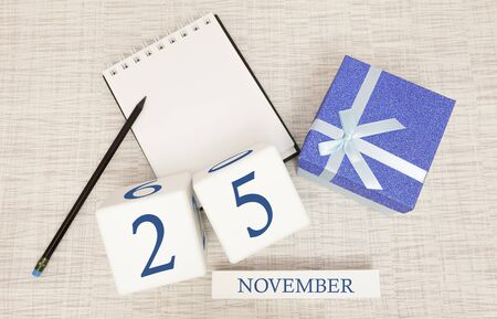 Notepad and wooden calendar for November 25, next to a blue gift box. Stock Photo