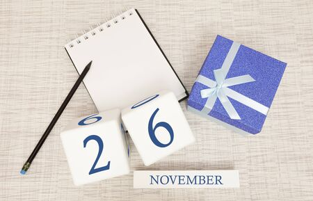 Notepad and wooden calendar for November 26, next to a blue gift box. Stock Photo