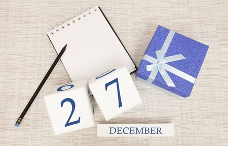 Cube calendar for December 27 and gift box, near a notebook with a pencil