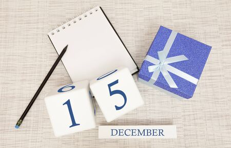 Cube calendar for December 15 and gift box, near a notebook with a pencil Imagens