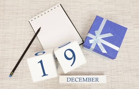 Cube calendar for December 19 and gift box, near a notebook with a pencil