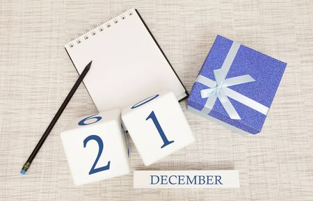 Cube calendar for December 21 and gift box, near a notebook with a pencil