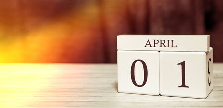 Calendar reminder event concept. Wooden cubes with numbers and month on April 1 with sunlight.