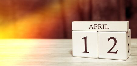 Calendar reminder event concept. Wooden cubes with numbers and month on April 12 with sunlight.