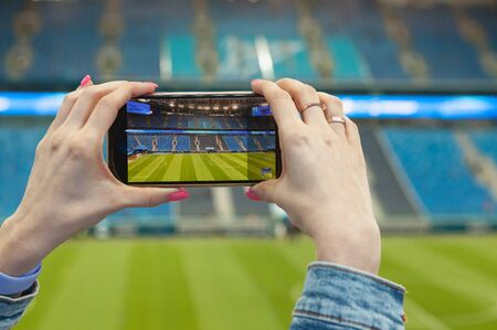 A girl in a football (soccer) stadium with a smartphone takes a picture of the green field of the arena. Modern technology at sports events. Stock Photo