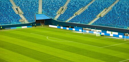 Football (soccer) stadium with a green lawn without spectators, end of the game