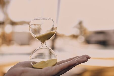 Hourglass in a female hand on a blurry light background, a symbol of the passage of time and the implementation of important life matters