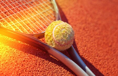Single tennis racket on a orange sand court with a tennis ball on a lighted background. Close-up 写真素材