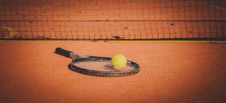 Tennis racket and yellow ball on hard orange court