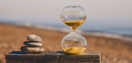 Sandglass on a wooden board with three stones in the form of a pyramid, a modern hourglass on a beach with golden sand against the background of the sea Reklamní fotografie