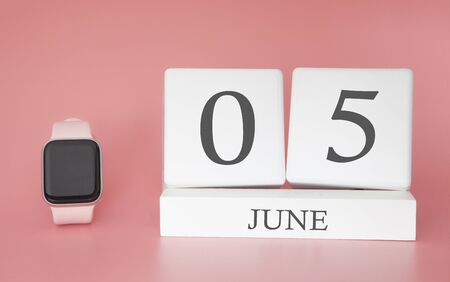 Modern Watch with cube calendar and date 05 june on pink background. Concept summer time vacation.